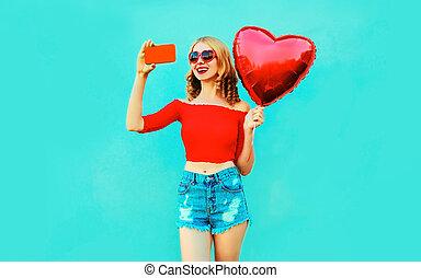 beau, image, femme, coloré, coeur, porter, prendre, formé, jeune, air, bleu, téléphone, short, fond, sourire, selfie, ballon rouge