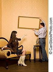 beau, image, femme, salle, séance, mur, sofa, cadre, pendre, jeune, contre, haut, regarder, autre, chaque, homme souriant