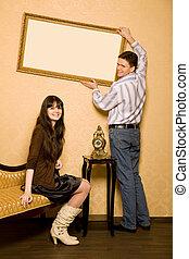 beau, image, femme, salle, séance, mur, sofa, cadre, pendre, jeune, haut, homme souriant