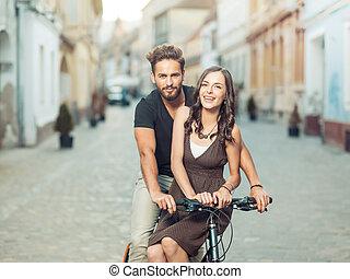 beau, jeune couple, bicyclette, dans ville