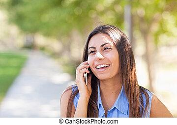 beau, jeune, ethnique, femme parler, sur, elle, smartphone, dehors.