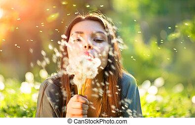 beau, jeune femme, coucher, sur, les, champ, dans, herbe verte, souffler pissenlits, et, sourire