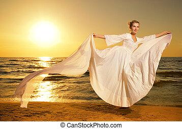 beau, jeune femme, danse, sur, a, plage, à, coucher soleil