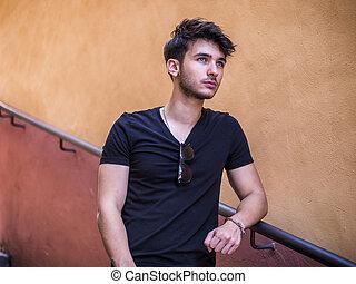 beau, jeune homme, debout, dans, ville européenne, rue