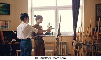 beau, jeunes femmes, étudiant, et, professionnel, artiste, are, peinture, ensemble, dans, atelier, prof, est, partage, expérience, et, donner, advice., talent artistique, et, créativité, concept.