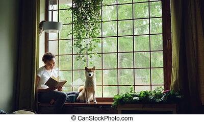 beau, mignon, femme, visible., ascendance, rebord fenêtre, rideaux, moderne, jeune, dog., regarder, dehors, livre, vert, ensemble, joli, intérieur, usines, séance, lecture