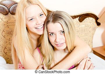beau, petites amies, lit, &, séance, deux, étreindre, jeune regarder, appareil photo, closeup, séduisant, blonds, amusant, portrait, sourire, femmes, pyjamas, blanc, heureux