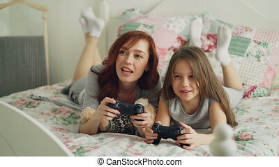 beau, peu, console, confortable, tv, mère, lit, matin, fille, quoique, jeux ordinateur, rire, avoir, chambre à coucher, amusement, maison, jouer, mensonge, heureux