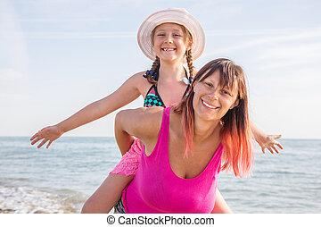 beau, plage., fille, elle, donner, cavalcade, avoir, ferroutage, femme, mère, amusement, portrait, fille souriant, heureux
