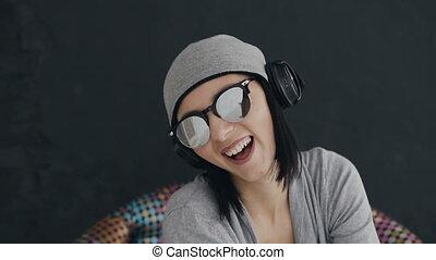 beau, porter, gros plan, femme, écouteurs, écoute, casquette, jeune, lunettes soleil, arrière-plan noir, amusement, musique, figure