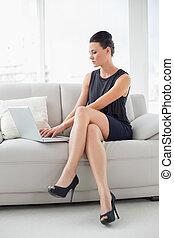 beau, puits habillé, femme aide ordinateur portatif, sur, sofa