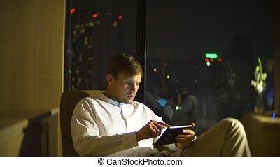 beau, salle, négligence, panoramique, jeune, arrière-plan., fenêtre, barbouillage, utilisation, chaise, homme, smartphone, night., gratte-ciel