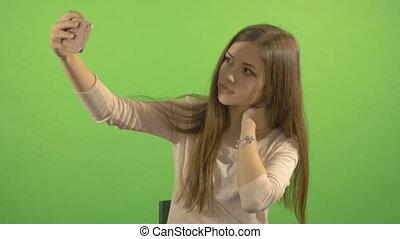 beau, smartphone, selfi, screen., jeune, sourire, arrière-plan vert, confection, modèle, blanc