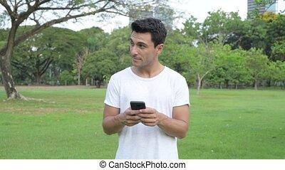 beau, téléphone, parc, jeune, hispanique, dehors, utilisation, homme, heureux