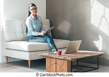 beau, touchpad, femme, bureau, fonctionnement, séance, jeune, divan, regarder, quoique, appareil photo, sourire, lunettes, multitasking.