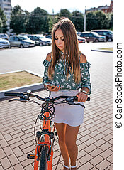 beau, ville, sien, smartphone, stands, main, skirt., bicycle., ensoleillé, ruelle, jour, femme, application, brunette, tenue, internet, lecture fille, blanc, il