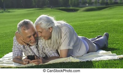 Beauiful senior woman joins husband with cellphone