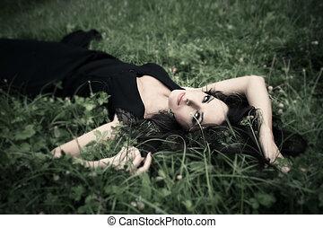 lie in grass - beauitful elegant mature woman lie in grass