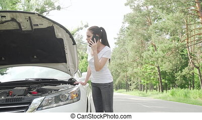 Beauitful woman looking under the hood of her broken car on countryside road