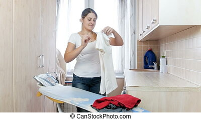 Beauitufl young woman ironing and carefully putting in pile clothes at laundry