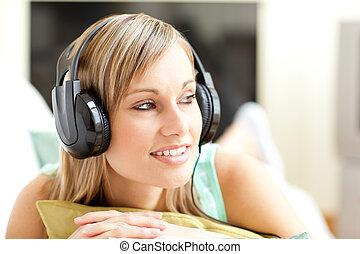 beautful, mujer joven, escuchar, música, acostado, en, un, sofá