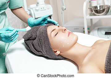 beautician applies face cream on beautiful young woman in Spa salon. cosmetic procedure skin care.