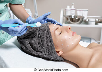 beautician applies face cream on young woman in Spa salon. cosme