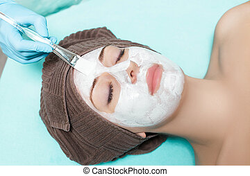 beautician applies face mask on beautiful young woman in Spa salon. cosmetic procedure skin care. Microdermabrasion