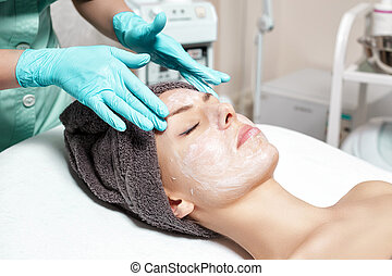 beautician applies face mask to beautiful young woman in Spa salon. cosmetic procedure skin care. Microdermabrasion