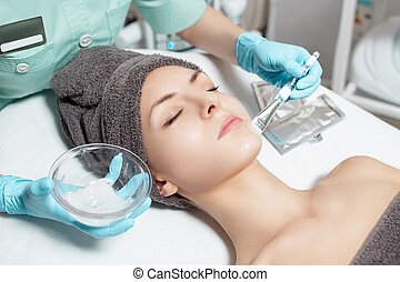 beautician applies face mask with brush to beautiful young woman in Spa salon. cosmetic procedure skin care.