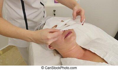 beautician applies facial mask to the girl's skin.