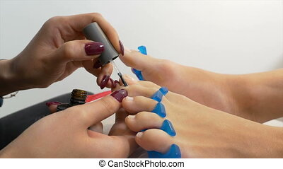 Beautician applies treatment on toe nails of client