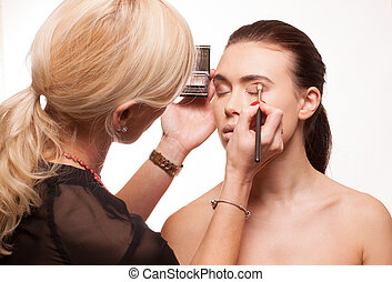 Beautician applying eye makeup to an attractive young model...