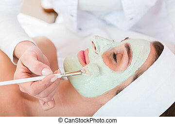 Beautician applying face peeling mask to woman