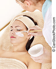 Beautician applying facial mask by woman. - Beautician...