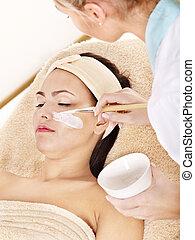 Beautician applying facial mask by woman. - Beautician...