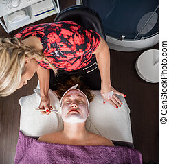 Beautician Applying Facial Mask To Woman In Salon
