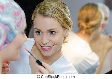 Beautician applying lipgloss to woman