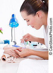 beautician applying manicure - young beautician applying...
