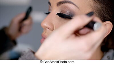 Beautician applying mascara - Beautician applying dark black...