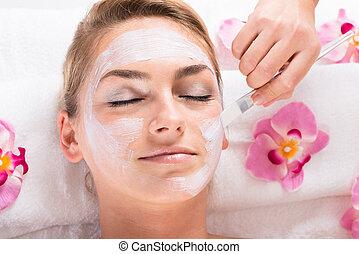 Beautician Applying Mask On Customer's Face At Salon