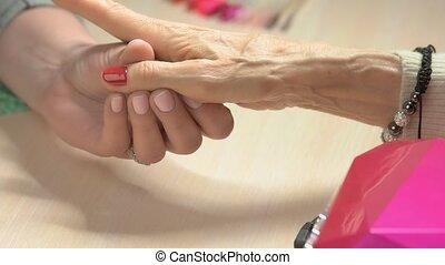 Beautician applying oil on manicured nails. Elderly woman...