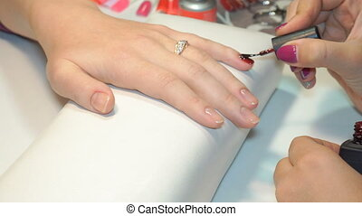beautician applying Polish nails to women nails - specialist...