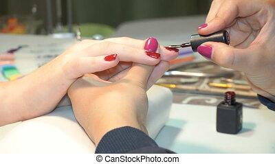 beautician applying Polish nails to women nails