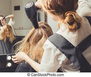 Beautician blow dry woman's hair at beauty salon