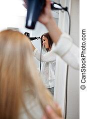 Beautician Blow Drying Hair Of Female Customer