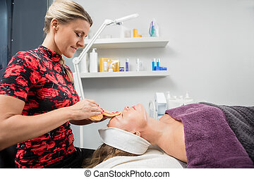 Beautician Cleansing Customer's Face With Sponge - Side view...