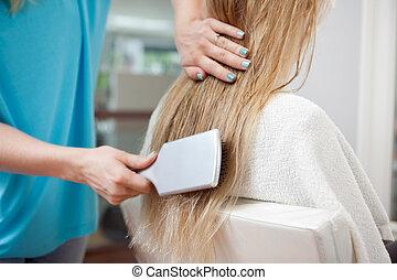 Beautician Combing Hair Of Customer
