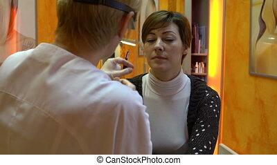 Beautician corrects woman's eyebrows - Beautician corrects...