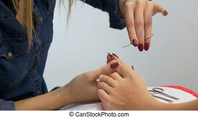 Beautician cuts the cuticles while performing professional...